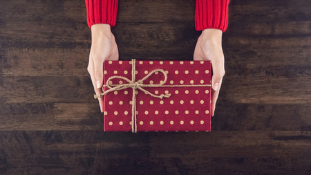 Woman hands giving christsmas gift box with red dotted paper top view on wood table background Imagens