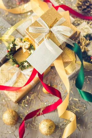 Pile of glittering silver and gold Christmas gift boxes with colorful ribbons and decorating items on wood table