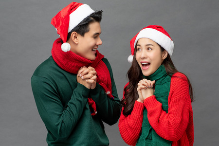 Excited happy young Asian couple wearing colorful Christmas theme clothes studio shot isolated on gray background