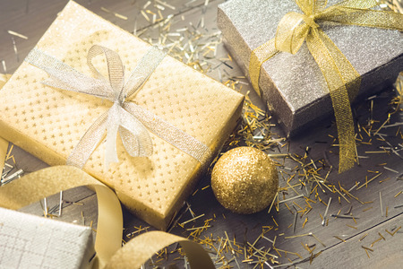 Sliver and gold shimmer Christmas gift boxes with glittering decoration items on wood table background