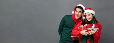 Happy smiling young Asian couple wearing colorful red and green sweaters with Christmas gift boxes studio shot on gray banner background