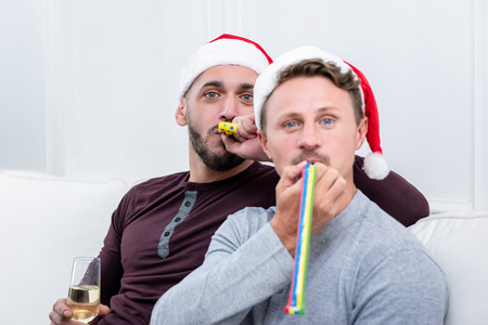 Playful gay couple blowing party horns while sitting on the couch celebrating Christmas together at home