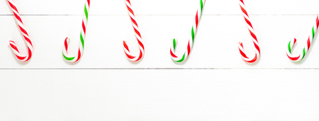 Colorful Christmas candy cane sweets on white wood banner backgground Imagens