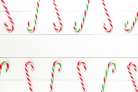 Colorful Christmas candy cane sweets on white wood backgground with copy space in the middle