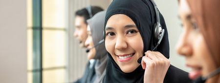 Friendly beautiful Asian muslim woman wearing microphone headset working as customer care operator with team in call center office, panoramic web banner