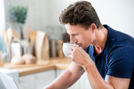 Casual man drinking coffee in the morning while seriously working on laptop computer at home