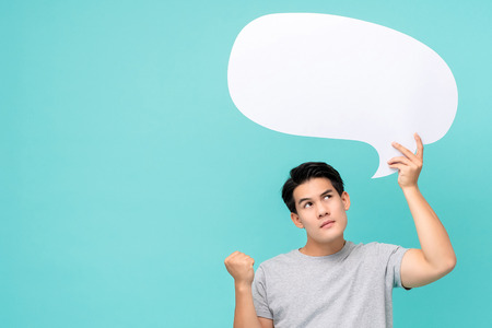 Curious young Asian man with empty speech bubble studio shot isolated on light blue background Imagens