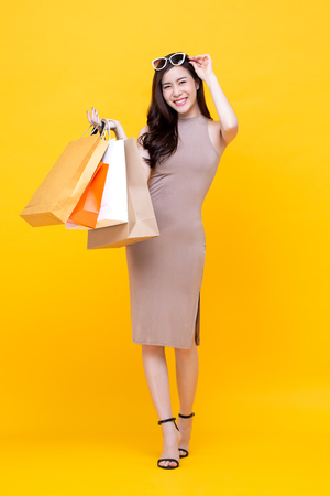 Happy beautiful Asian shopaholic woman carrying shopping bags in colorful yellow background for summer sale concept Imagens
