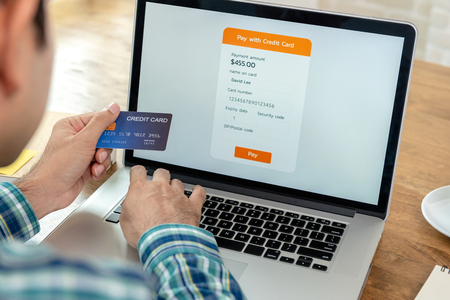 Young man filling credit card information making payment online in website with laptop computer
