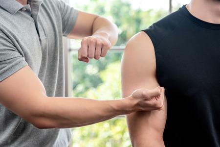Terapeuta maschio che dà massaggio al paziente maschio atleta battendo e martellando tecniche in clinica, concetto di terapia fisica sportiva