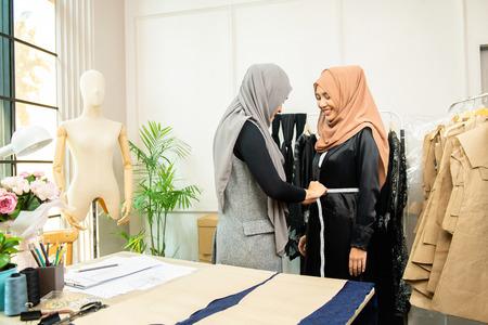 Woman asian muslim designer measuring waist of customer inside a tailor shop Banque d'images