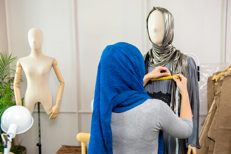 Woman muslim designer measuring a mannequin in a tailor  shop by using a measuring tape