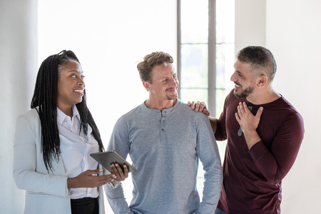 Happy mature male gay couple having a discussion with a female african real estate agent about purchasing new house