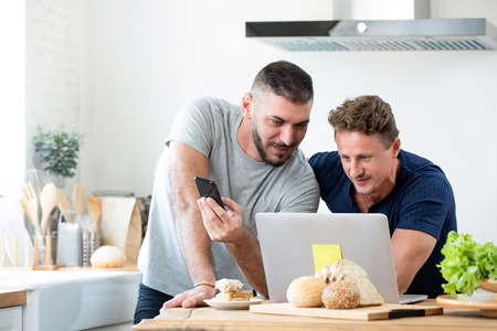 Fit mature male caucasian gay couple having breakfast while  surfing internet on laptop together at home
