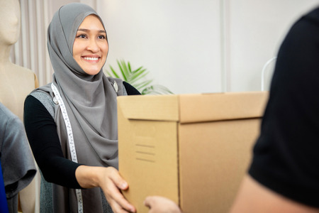 Muslim woman designer receiving parcel box from delivery man at her tailor shop