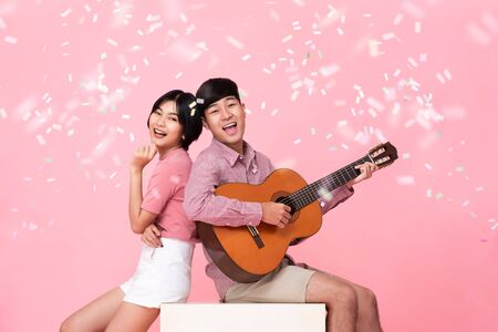 Happy young Asian man playing guitar and singing with his girlfriend studio shot on pink background