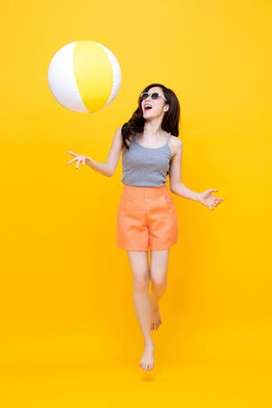 Feliz joven mujer asiática en ropa casual de verano jugando pelota de playa en fondo amarillo colorido