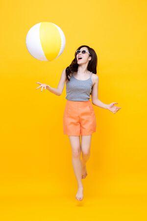 Szczęśliwa młoda Azjatycka kobieta w swobodnych letnich ubraniach grająca w piłkę plażową na kolorowym żółtym tle
