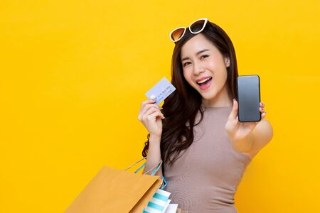 Beautiful Asian woman with shopping bags showing credit card and smartphone in hands for mobile financial application concept