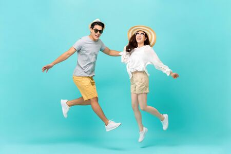 Playful energetic Asian couple in summer beach casual clothes jumping isolated on light blue background studio shot 版權商用圖片