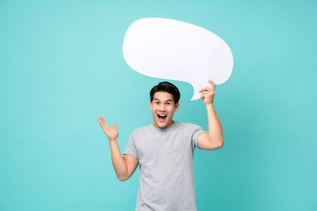 Excited young Asian man holding speech bubble with empty space for text studio shot isolated on light blue background