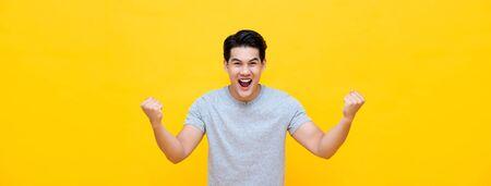 Opgewonden jonge Aziatische man die zijn vuisten opheft met een lachend opgetogen gezicht, ja gebaar, succes vierend op gele bannerachtergrond