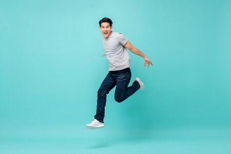 Energetischer glücklicher junger asiatischer Mann in Freizeitkleidung springen, Studioaufnahme einzeln in hellblauem Hintergrund