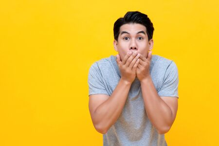 Shocked man with hands covering mouth in colorful yellow background