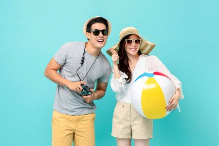 Lovely Asian couple in summer casual clothes with beach accessories studio shot isolated on light blue background