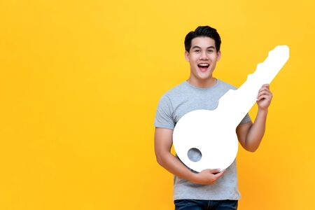 Excited young Asian man holding big mockup car key studio shot in yellow background with copy space