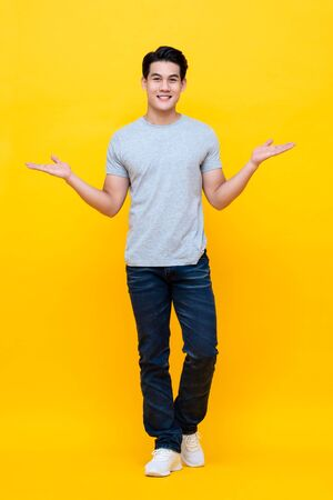 Full body of young happy handsome Asian man raising his hands with open palms gesture studio shot isolated on colorful yellow background 스톡 콘텐츠