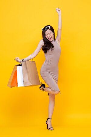 Felice donna asiatica eccitata con borse della spesa in vendita concetto, studio shot isolato su sfondo giallo colorato