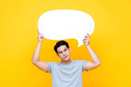 Unhappy bored young Asian man with empty speech bubble on colorful yellow background