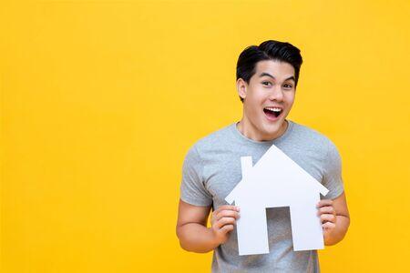 Portret van een jonge, blije, opgewonden Aziatische man die papier thuis vasthoudt voor een vastgoedconcept Stockfoto