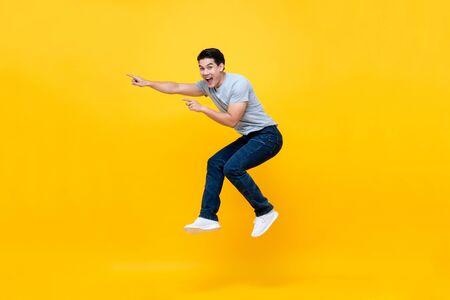 Energetischer aufgeregter junger asiatischer Mann, der springt und Hand auf leeren Raum beiseite zeigt Studioaufnahme einzeln auf buntem gelbem Hintergrund