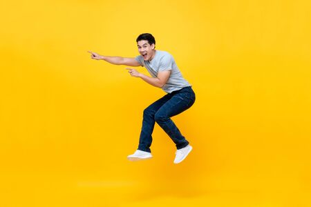 Giovane asiatico eccitato energico che salta e indica la mano verso lo spazio vuoto da parte studio shot isolato su sfondo giallo colorato