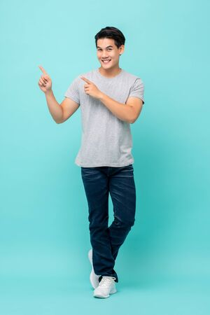 Confident smiling young Asian man pointing hands to empty space aside studio shot isolated on light blue background
