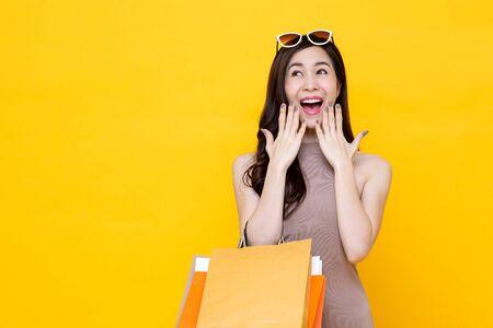 Mujer asiática joven que lleva coloridas bolsas de la compra en el estudio de gesto sorprendido y emocionado tiro aislado sobre fondo amarillo con espacio de copia Foto de archivo