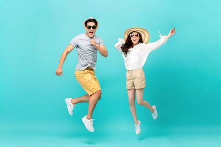 Figlarna, energiczna azjatycka para w letnich ubraniach na plaży, skaczących na białym tle na jasnoniebieskim tle studio strzał