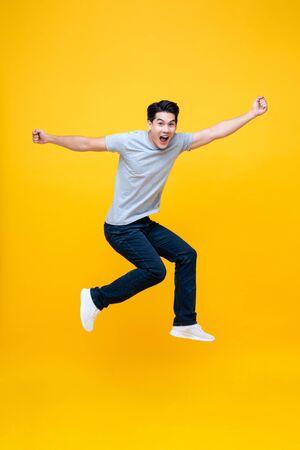 Energetischer aufgeregter junger asiatischer Mann in Freizeitkleidung, der Studioaufnahme einzeln in buntem gelbem Hintergrund springt Standard-Bild