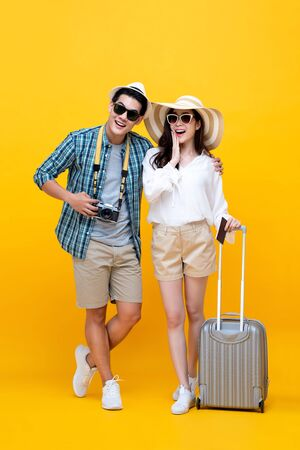 Feliz pareja de jóvenes turistas asiáticos emocionados en colorido fondo amarillo Foto de archivo