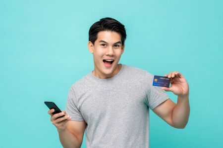 Handsome smiling young Asian man with credit card and smartphone in hand, mobile payment concept