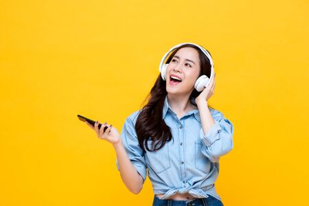 Happy young Asian woman wearing wireless headphones listening to music from smartphone studio shot isolated on yellow background
