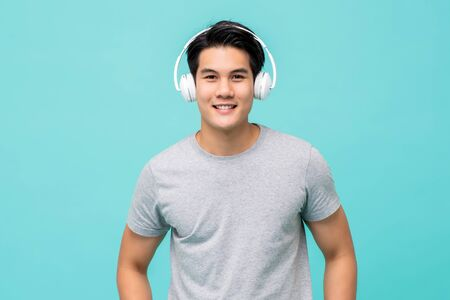 Young smiling handsome Asian man wearing wireless headphones listening to music in light blue background