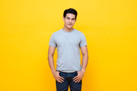 Handsome young Asian man in plain light gray t-shirt studio shot isolated on colorful yellow background 写真素材