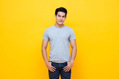 Hombre asiático joven hermoso en tiro del estudio de la camiseta gris claro llano aislado en fondo amarillo colorido