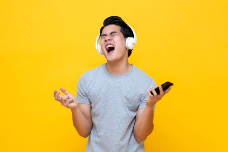Giovane uomo asiatico che indossa le cuffie cantando e urlando mentre ascolta musica rock dallo smartphone