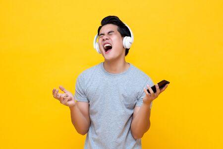 Jonge Aziatische man met een koptelefoon die zingt en schreeuwt terwijl hij naar rockmuziek van een smartphone luistert
