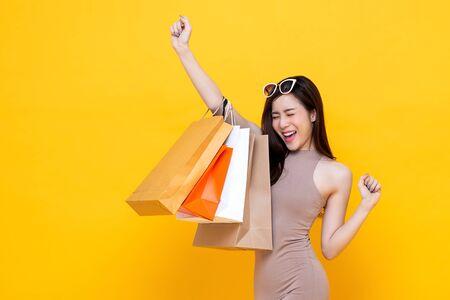 Gelukkig opgewonden Aziatische vrouw die boodschappentassen draagt met de hand die studio-opname opheft, geïsoleerd op een kleurrijke gele achtergrond