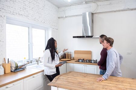 Female real estate agent in kitchen showing couple around new house